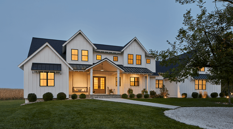 Large White Home with Lit Windows and Wood Entry Door