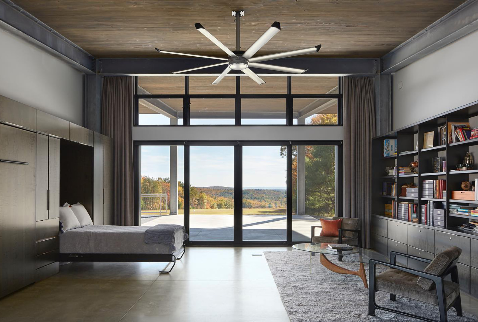Modern contemporary bedroom has a wall with black sliding patio door and many black picture windows.