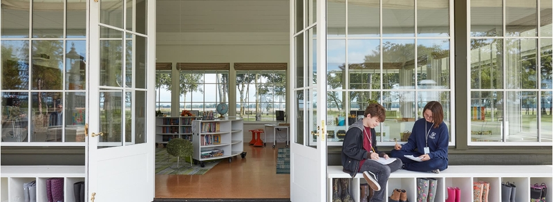 two children sitting outside a school library with pella windows and doors
