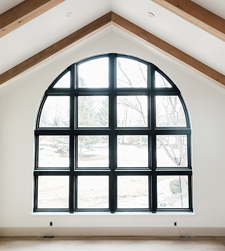 Large custom arched black window in remodeled home