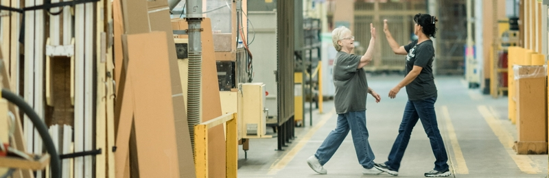 Pella Employees High-five in Factory