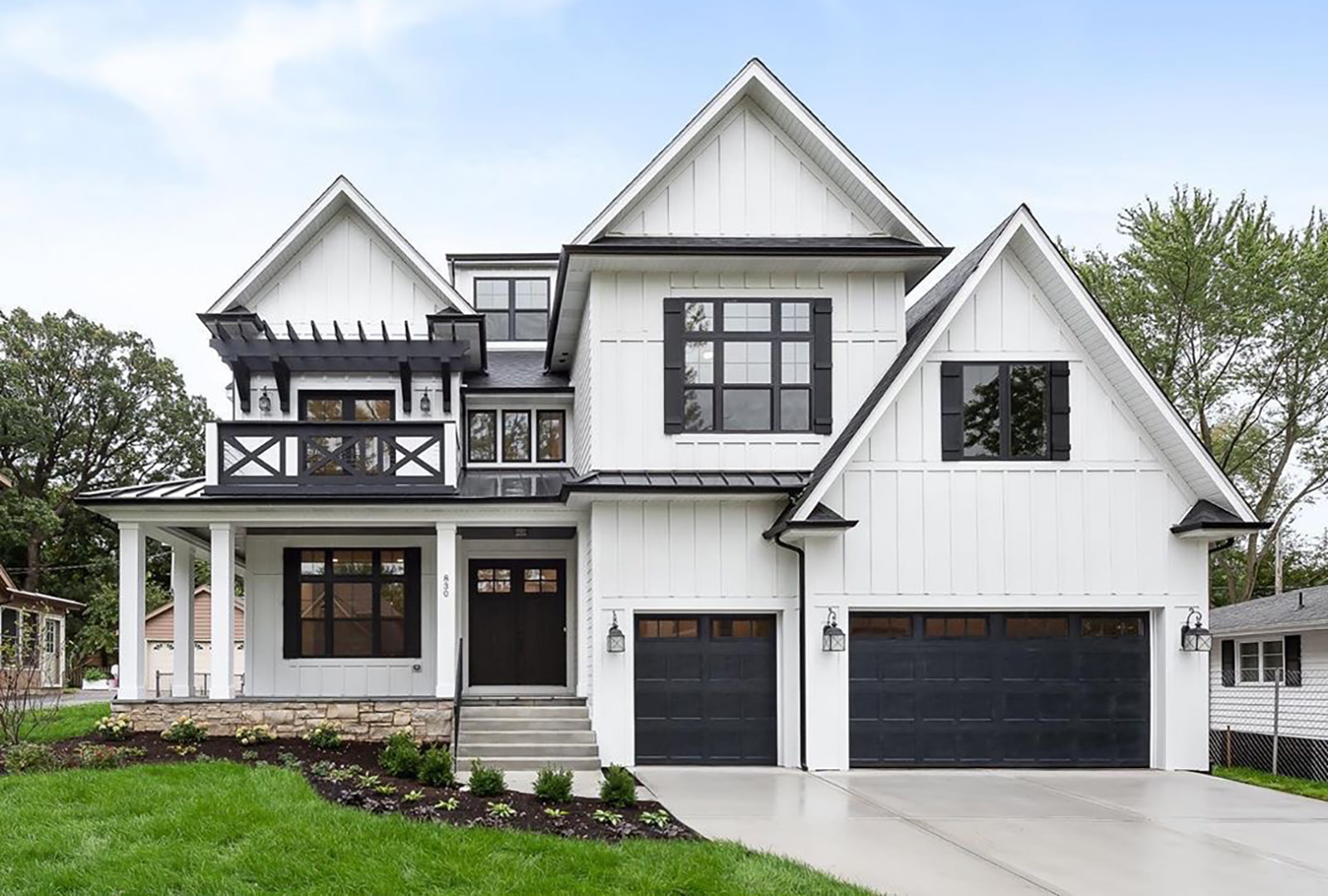 Exterior view of white farmhouse-style home with several black windows.
