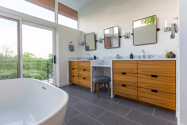 Modern bathroom with wood double vanities and wall of glass with fixed windows and sliding patio door
