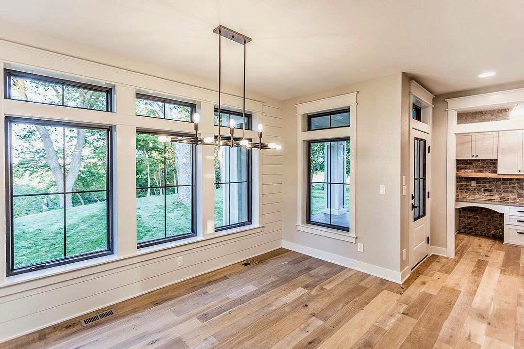 black window frames with white trim in a room with shiplap walls and wood flooring