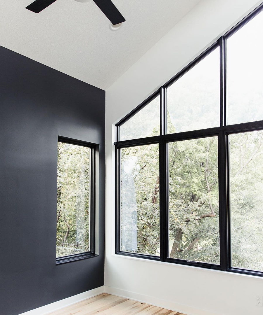 A white wall features a custom shape black window that aligns with the shape of the roofline.
