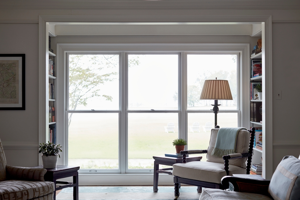 Three floor-to-ceiling double-hung windows flanked by bookcases on either side in living room