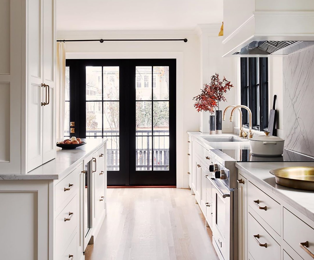 A white narrow kitchen has black hinged french patio doors on the far wall.