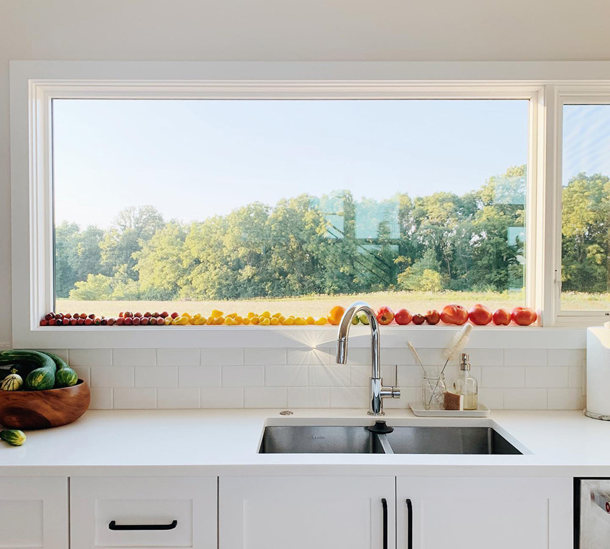 A white rectangular window over the kitchen sink acts as a shelf for resting an array of colorful produce.