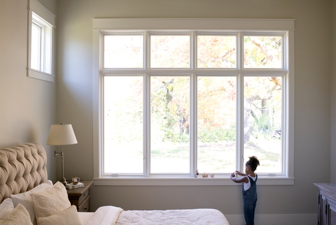 Girl playing with toys by painted white windows with white trim in bedroom