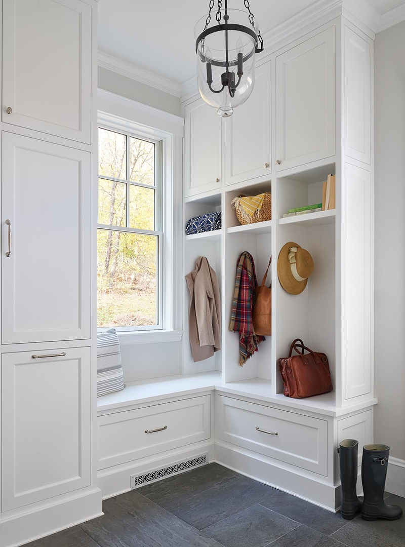 A white mudroom is brightened by a white double-hung window between the storage cabinets.