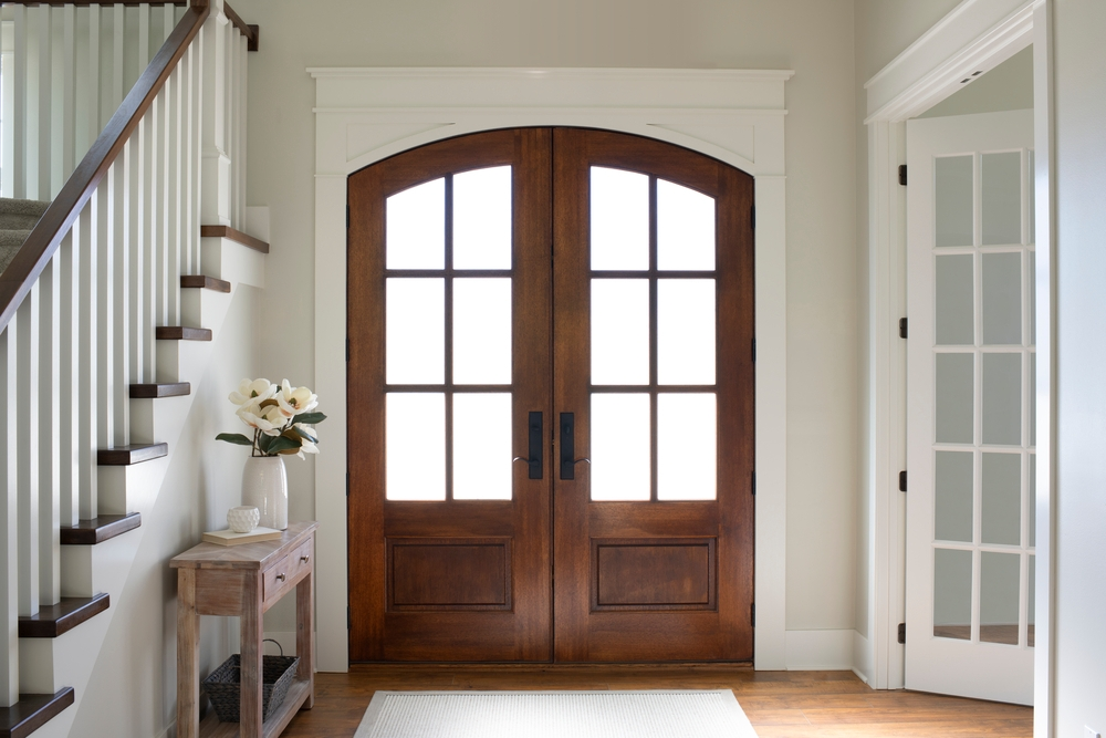 White interior entryway with a wood double door with an arched top and traditional grilles on the 3/4 glass