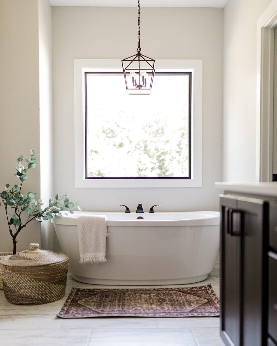 Square picture window over bathtub lets light into spa like bathroom