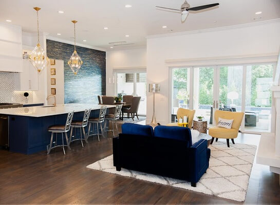 Open concept living room and dining room with sliding patio doors and navy couch and kitchen island