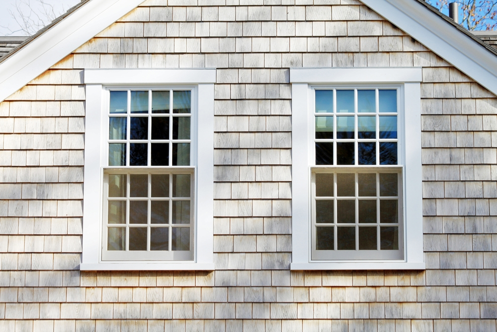 Two white double-hung windows with traditional grilles on shingle siding farmhouse