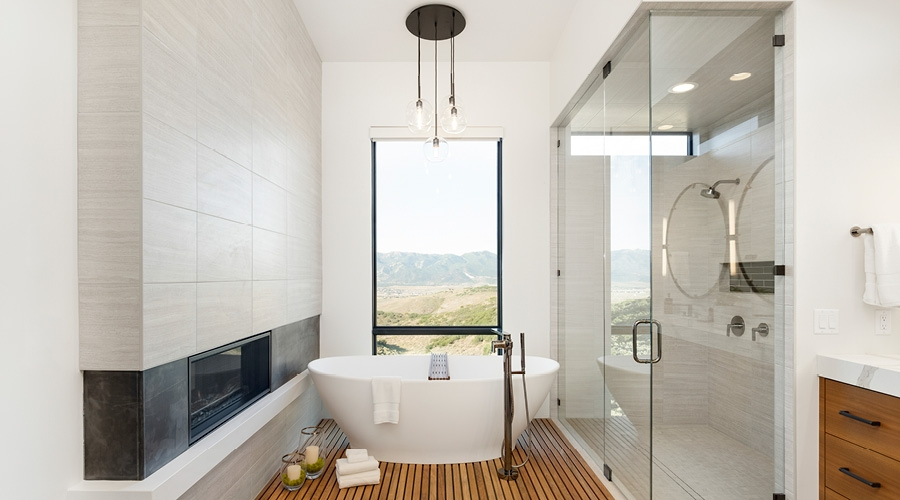 Tall Window Behind Tub Next to Fireplace and Shower