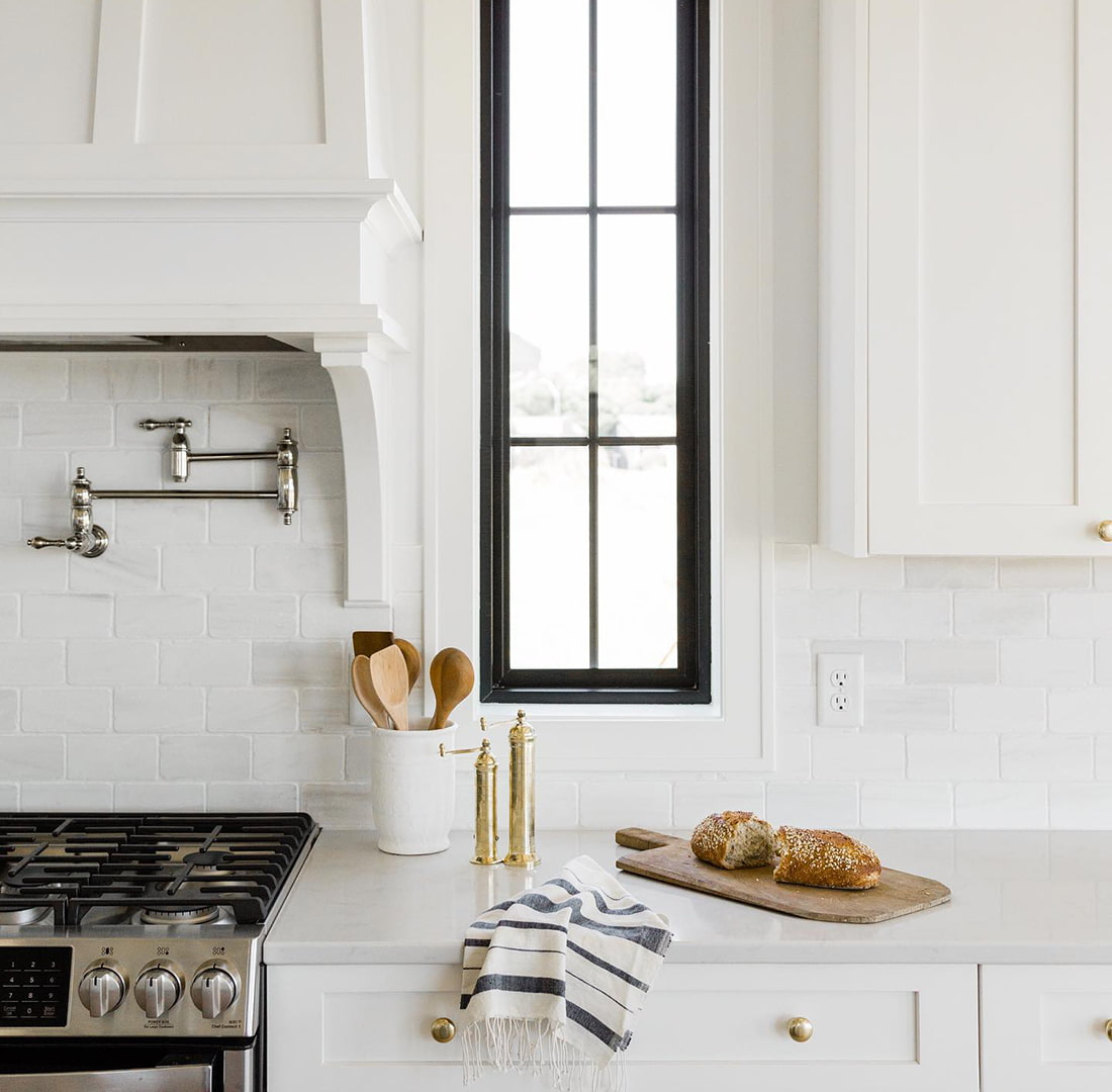 A rectangle picture window sits between the hood of the stove and kitchen cabinets.