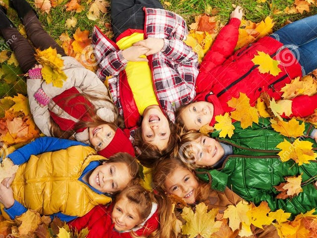 kids-lay-autumn-grass-large-group-laying-maple-leaves-all-over-them-day-34946330.jpg